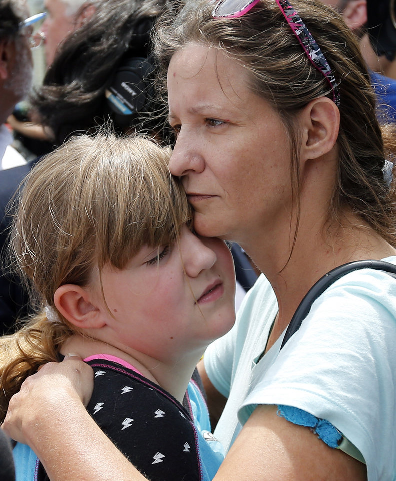 Photo - Geri Boyles of Lowell, Mass. hugs her daughter, Corinna, 10, outside a burned three-story apartment and business building in Lowell, Thursday, July 10, 2014. The neighbors lost people they knew in the fast-moving pre-dawn fire where officials said seven people died. (AP Photo/Elise Amendola)
