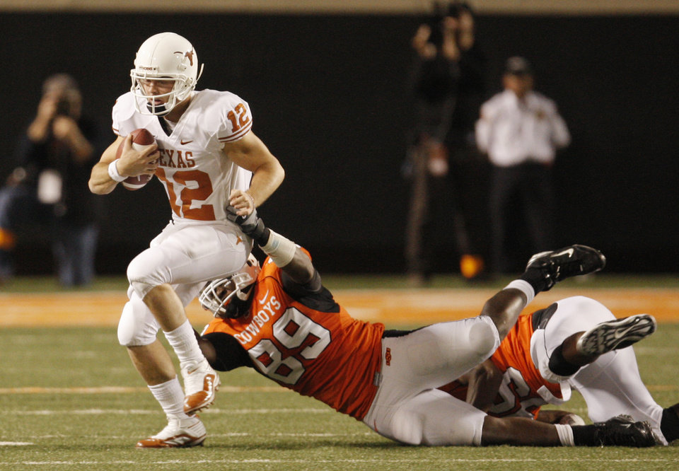 Photo - Cooper Bassett (89) of OSU tries to bring down Texas quarterback Colt McCoy during the college football game between the Oklahoma State University Cowboys (OSU) and the University of Texas Longhorns (UT) at Boone Pickens Stadium in Stillwater, Okla., Saturday, Oct. 31, 2009. Photo by Doug Hoke, The Oklahoman