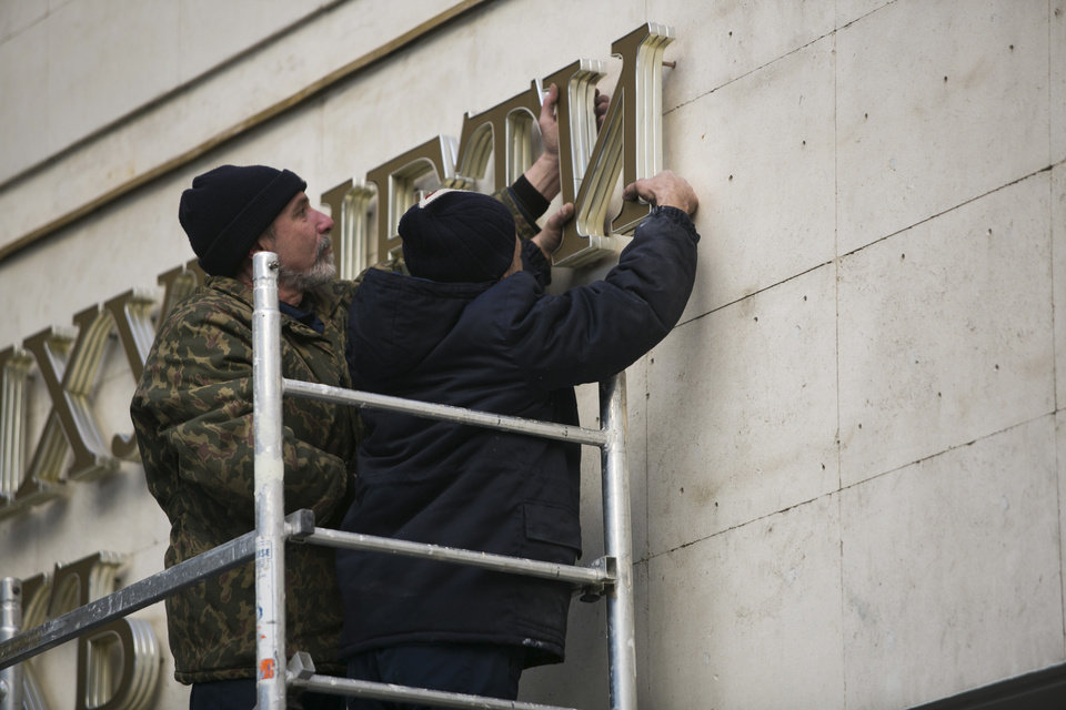 Photo - In this photo taken on Tuesday, March 18, 2014, workers remove old letters from the Crimea Parliament's building in Simferopol, Crimea. In a gilded Kremlin hall used by czars, Vladimir Putin redrew Russia's borders Tuesday by declaring the Crimean Peninsula part of the motherland - provoking a surge of emotion among Russians who lament the loss of empire and denunciations from Western leaders who called Putin a threat to the world. (AP Photo/Alexander Khitrov)