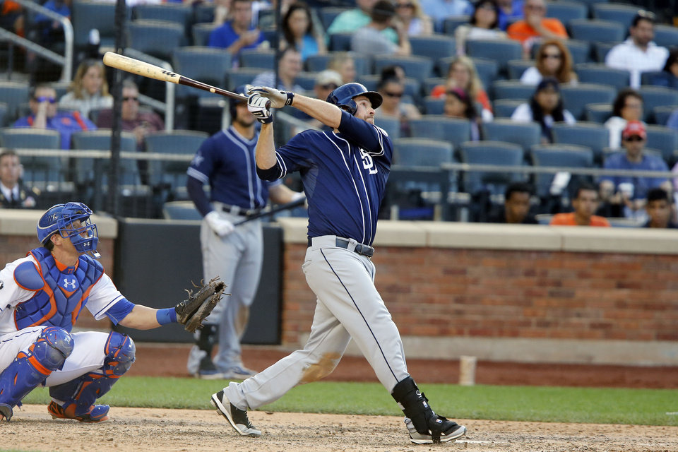 Photo - San Diego Padres' Chase Headley, right, follows through after hitting a solo home run during the eighth inning of a baseball game against the New York Mets, Saturday, June 14, 2014, in New York. (AP Photo/Jason DeCrow)