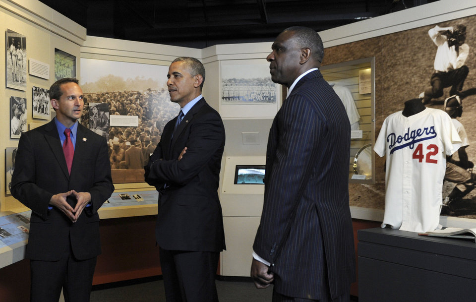 Photo - President Barack Obama, accompanied by Baseball Hall of Fame President Jeff Idelson, left, and baseball hall of fame member Andre Dawson, inducted in 2010, looks over a collection item from Jackie Robinson during a tour the Baseball Hall of Fame in Cooperstown, N.Y., Thursday, May 22, 2014. Obama visited the museum to highlight tourism and steps to help spur international visits to the 50 states. Obama said the overall U.S. economy and local businesses will benefit if it isn't a hassle for people from other countries to visit the U.S. and spend money at its hotels, restaurants, tourist destinations and other businesses. (AP Photo/Susan Walsh)