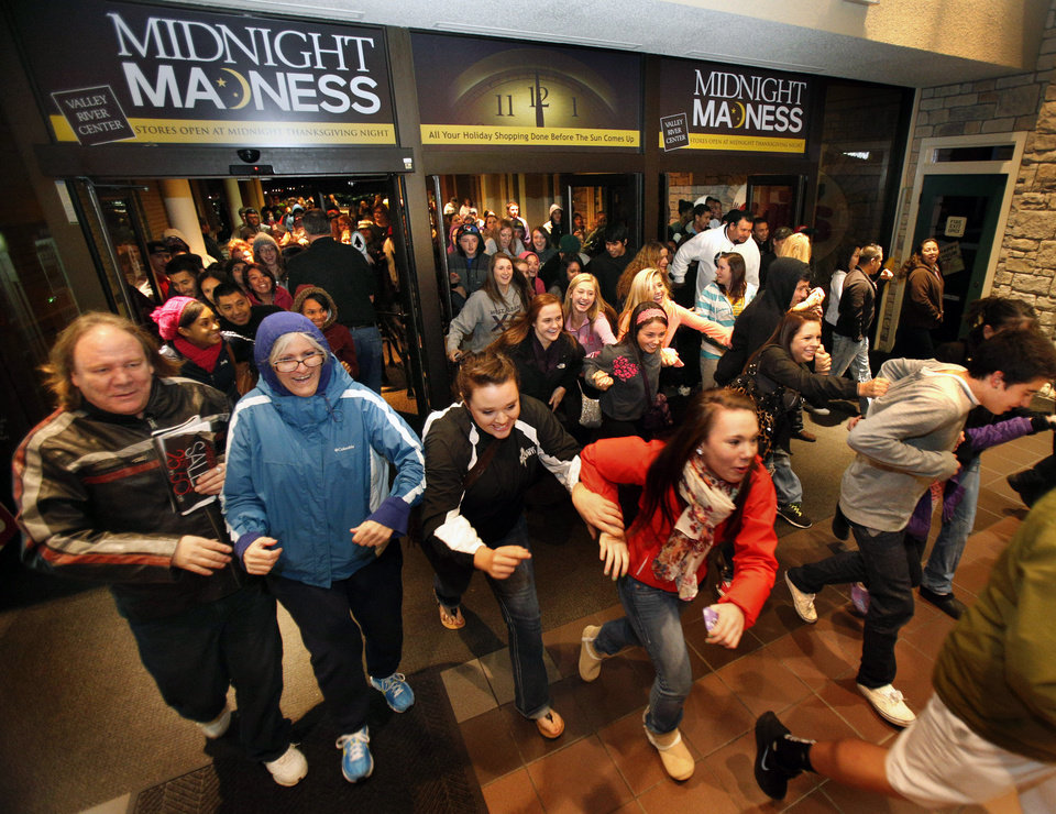 Photo -   Black Friday shoppers pour into the Valley River Center mall for the Midnight Madness sale Friday, Nov. 23, 2012 in Eugene, Ore. For decades, stores have opened their doors in wee hours of the morning on the day after Thanksgiving known as Black Friday. But this year, that changed when major chains from Target to Toys R Us opened on Thanksgiving itself, turning the traditional busiest shopping day of the year into a two-day affair. (AP Photo/The Register-Guard, Brian Davies)