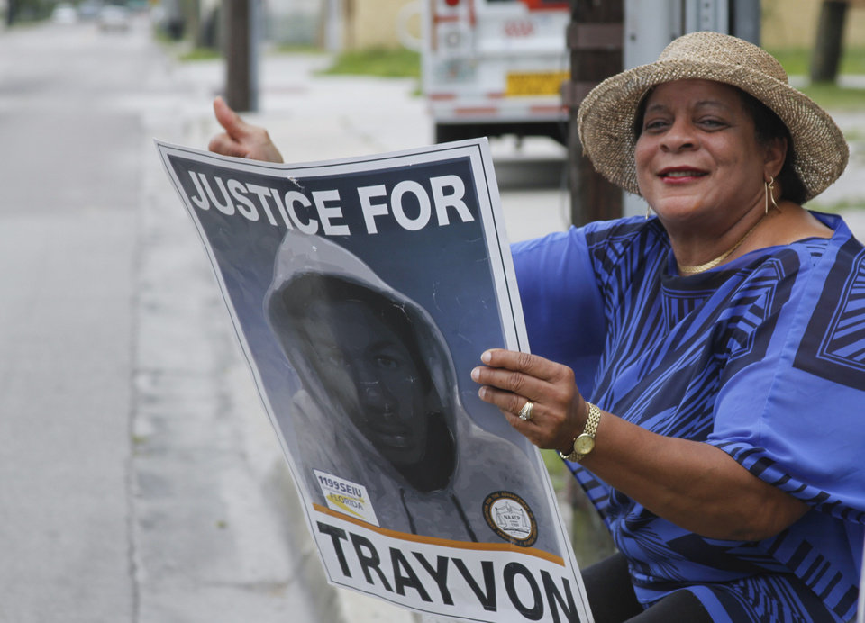Photo - Emma Encarnacion holds a sign and waves to passing motorists in front of her home in the Goldsboro Historical neighborhood, Saturday, July 13, 2013, in Sanford, Fla., while waiting for word on the verdict in the George Zimmerman trial. Zimmerman has been charged with the 2012 shooting death of Trayvon Martin. (AP Photo/Mike Brown) ORG XMIT: FLJR109