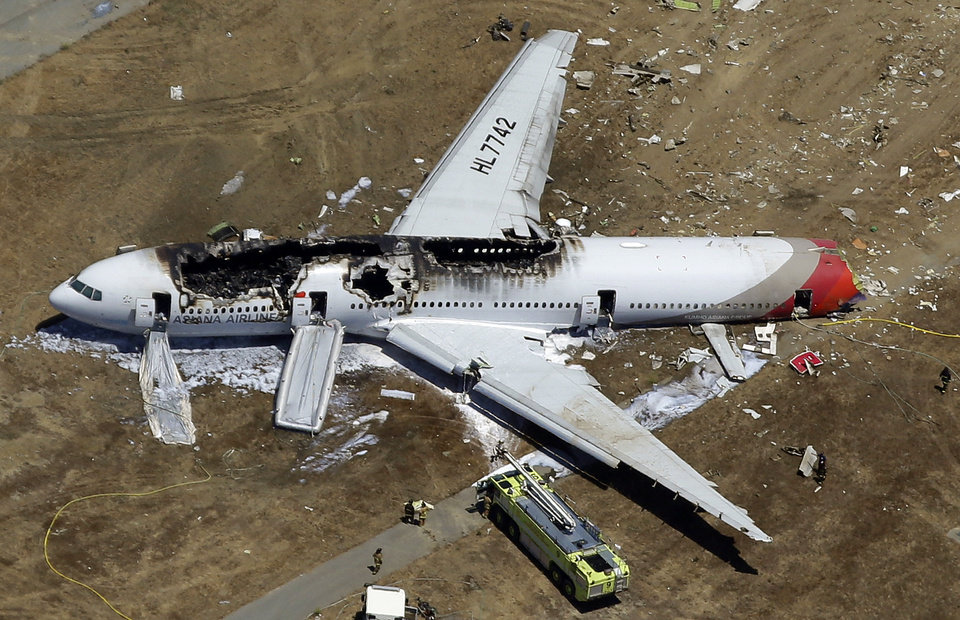 Photo - FILE - In this July 6, 2013 aerial file photo, the wreckage of Asiana Flight 214 lies on the ground after it crashed at the San Francisco International Airport in San Francisco. Nearly a year after Asiana Flight 214 crashed while landing in San Francisco, the National Transportation Safety Board is meeting to determine what went wrong, who's to blame and how to prevent future accidents. (AP Photo/Marcio Jose Sanchez, File)