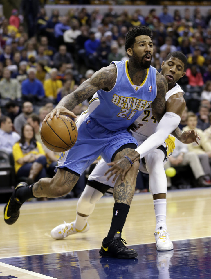 Photo - Indiana Pacers forward Paul George, right, reaches around Denver Nuggets forward Wilson Chandler (21) as he drives the baseline in the first half of an NBA basketball game in Indianapolis, Monday, Feb. 10, 2014.  (AP Photo/Michael Conroy)