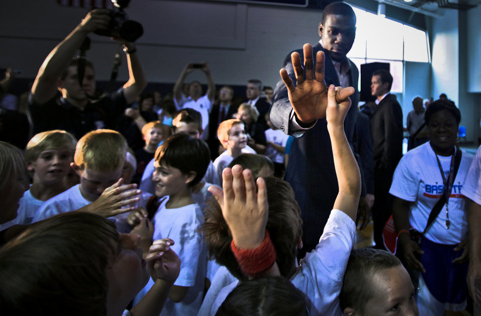 Photo - Kevin Durant greets basketball camp participants with high fives after a press conference to officially announce Durant's  five-year contract extension to play for the Oklahoma City Thunder on Friday, July 9, 2010, in Oklahoma City, Okla.   Photo by Chris Landsberger, The Oklahoman