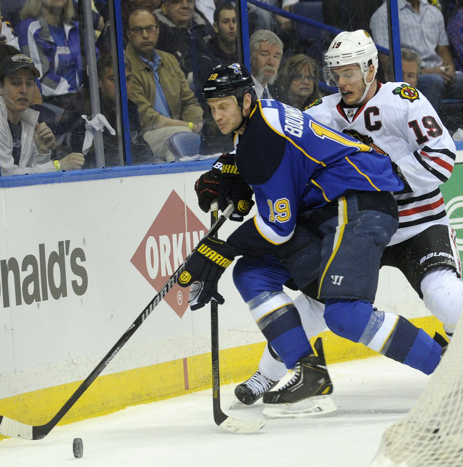 Photo - St. Louis Blues' Jay Bouwmeester, left, and Chicago Blackhawks' Jonathan Toews, right, battle for the puck during the first period in Game 2 of a first-round NHL hockey playoff series on Saturday, April 19, 2014, in St. Louis. (AP Photo/Bill Boyce)