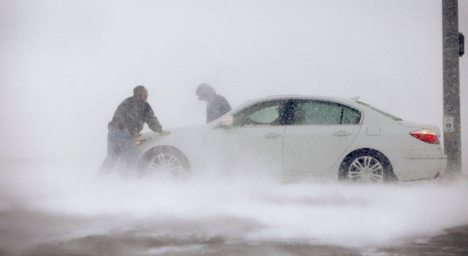 Photo - A driver receives help Thursday after getting stuck on Britton Road.  Photo by Bryan Terry, The Oklahoman