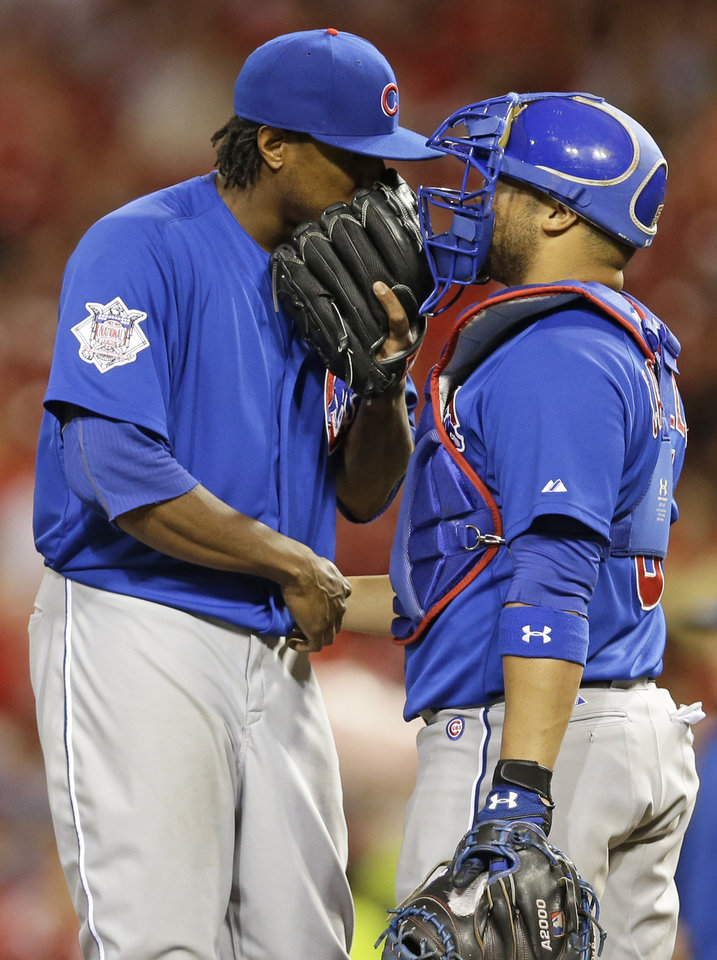 Photo - Chicago Cubs starting pitcher Edwin Jackson talks with catcher Welington Castillo, right, in the fifth inning of a baseball game against the Cincinnati Reds, Monday, July 7, 2014, in Cincinnati. (AP Photo/Al Behrman)