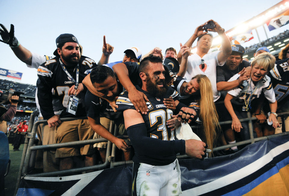 Photo - San Diego Chargers free safety Eric Weddle (32) is mobbed by fans after an NFL football game against the Kansas City Chiefs on Sunday, Dec. 29, 2013, in San Diego. The Chargers won 27-24 in overtime.  (AP Photo/Denis Poroy)