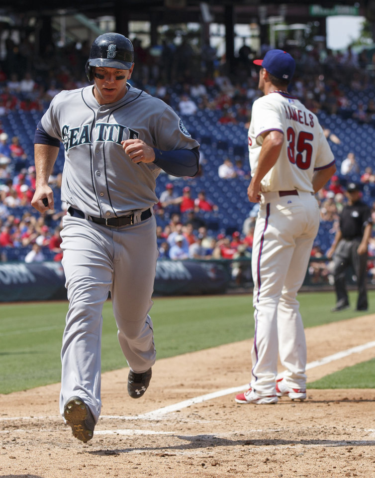 Photo - Seattle Mariners' Logan Morrison, left, scores on the wild pitch by Philadelphia Phillies starting pitcher Cole Hamels during the fourth inning of a baseball game, Wednesday, Aug. 20, 2014, in Philadelphia. (AP Photo/Chris Szagola)
