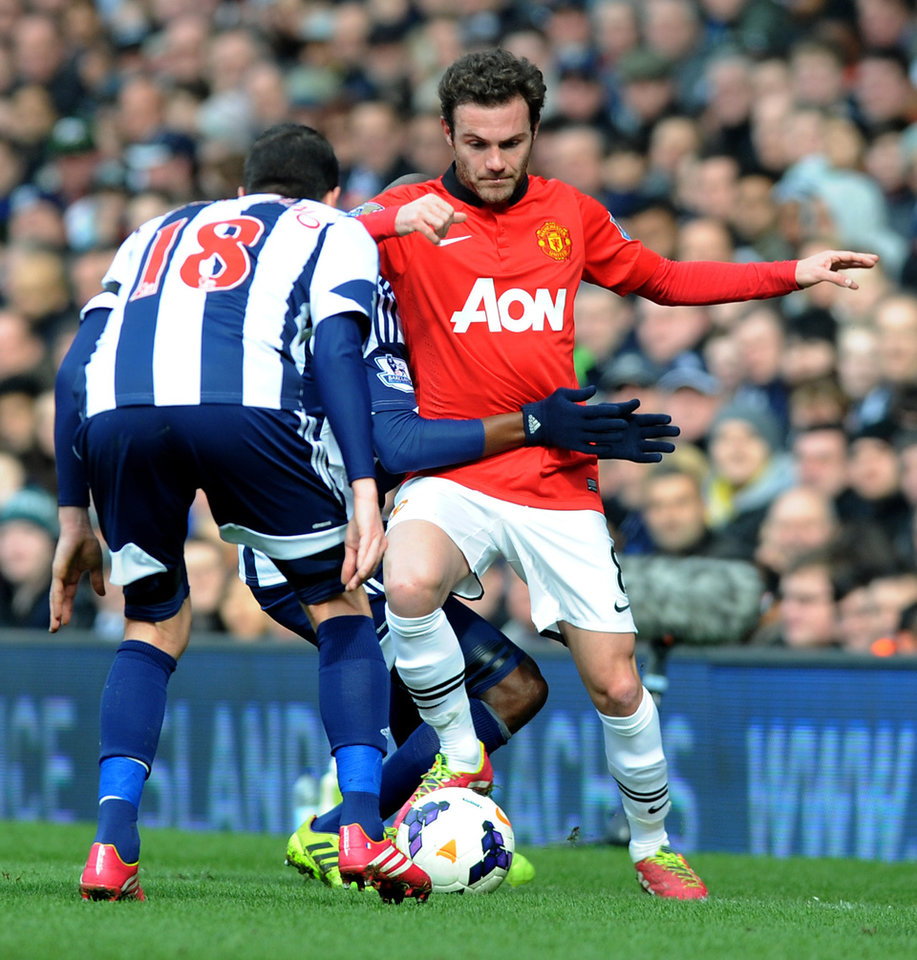 Photo - Manchester United's Juan Mata is held back by  West Brom's Youssuf Mulumbu  during the English Premier League soccer match between West Bromwich Albion and Manchester United at The Hawthorns Stadium in West Bromwich, England, Saturday, March 8, 2014.  (AP Photo/Rui Vieira)