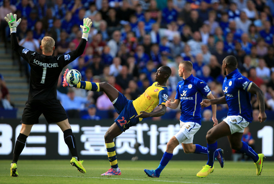 Photo - Arsenal's Yaya Sanogo, center, attempts to loft the ball over Leicester City's Kasper Schmeichel during their English Premier League soccer match against Leicester City at the King Power Stadium, Leicester, England, Sunday, Aug. 31, 2014. (AP Photo/Nick Potts, PA Wire)     UNITED KINGDOM OUT    -   NO SALES   -   NO ARCHIVES