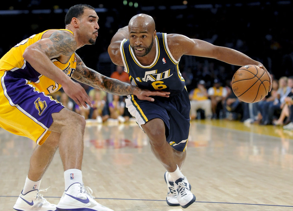 Photo -   Utah Jazz guard Jamaal Tinsley (6) gets by Los Angeles Lakers center Robert Sacre (50) as he drives to the basket in the first half of an NBA preseason basketball game, Saturday, Oct. 13, 2012, in Los Angeles. (AP Photo/Gus Ruelas)