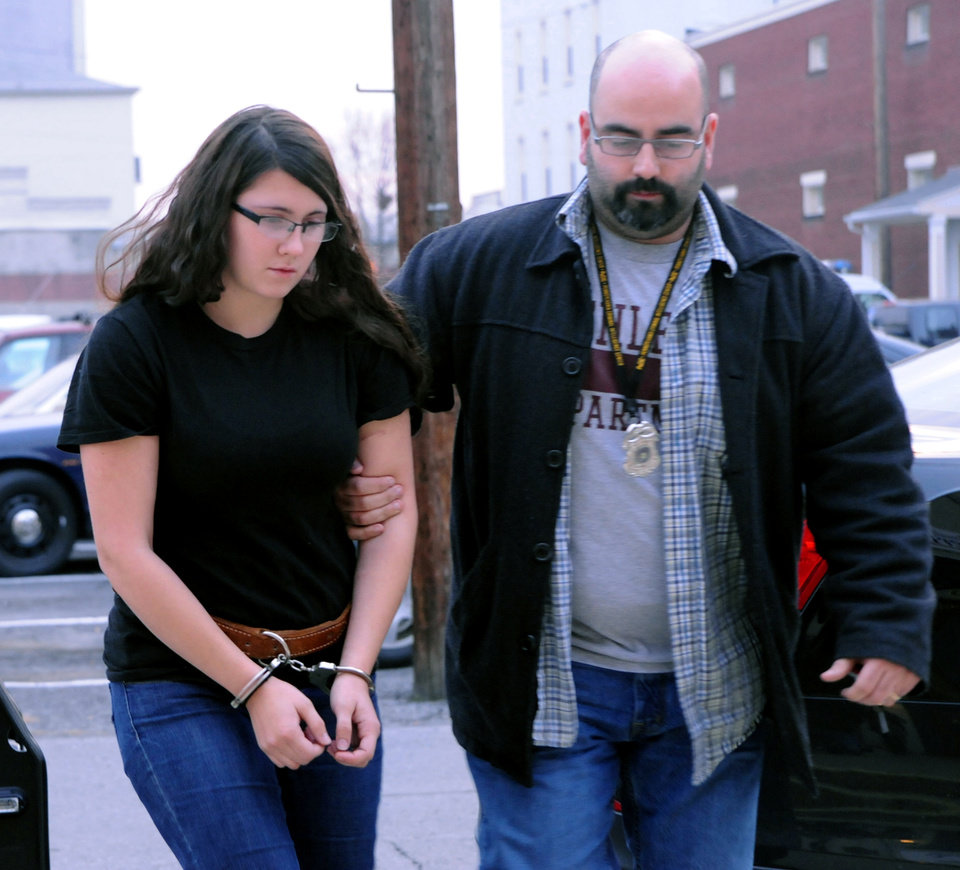 Photo - FILE - In this Tuesday, Dec. 3, 2013 file photo, Miranda K. Barbour is led into District Judge Ben Apfelbaum's office in Sunbury, Pa., by Sunbury policeman Travis Bremigen. In an interview with The Daily Item newspaper published Feb. 15, 2014, Barbour, charged along with her newlywed husband Elytte Barbour in the murder of a man they met through Craigslist, admitted to the slaying and said she has killed more than 20 others across the country, claims police said they are investigating.  (AP Photo/The News-Item, Mike Staugaitis, File)  MANDATORY CREDIT