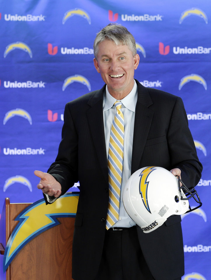 Photo - New San Diego Chargers head coach Mike McCoy laughs as he holds a team helmet during an NFL football news conference, Tuesday, Jan. 15, 2013, in San Diego. The former offensive coordinator for the Denver Broncos replaces Norv Turner, who was fired along with general manager A.J. Smith after the Chargers finished 7-9 and missed the playoffs for the third straight season. (AP Photo/Gregory Bull)