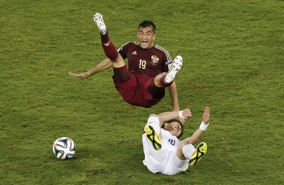 Photo - South Korea's Ki Sung-yueng, bottom, fouls Russia's Alexander Samedov during the group H World Cup soccer match between Russia and South Korea at the Arena Pantanal in Cuiaba, Brazil, Tuesday, June 17, 2014. (AP Photo/Thanassis Stavrakis)