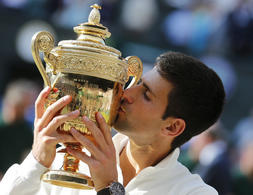 Photo - FILE - In this July 6, 2014, file photo, Novak Djokovic of Serbia kisses the trophy after defeating Roger Federer of Switzerland in the men's singles final at the All England Lawn Tennis Championships in Wimbledon, London. Heading into the U.S. Open, Roger Federer, Rafael Nadal,  Djokovic and Andy Murray have won 36 of the past 38 Grand Slam titles, a stretch dating to the 2005 French Open. Nowadays, there seems to be a growing sense _ or hope, maybe _ among the best of the rest on the men's tennis tour that the quartet might be more vulnerable than ever. (AP Photo/Ben Curtis, File)