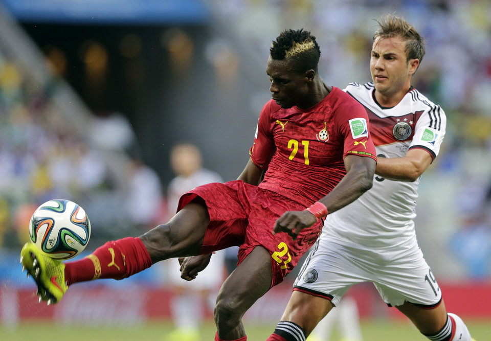 Photo - Ghana's John Boye, left, clears the ball from Germany's Mario Goetze during the group G World Cup soccer match at the Arena Castelao in Fortaleza, Brazil, Saturday, June 21, 2014. (AP Photo/Matthias Schrader)