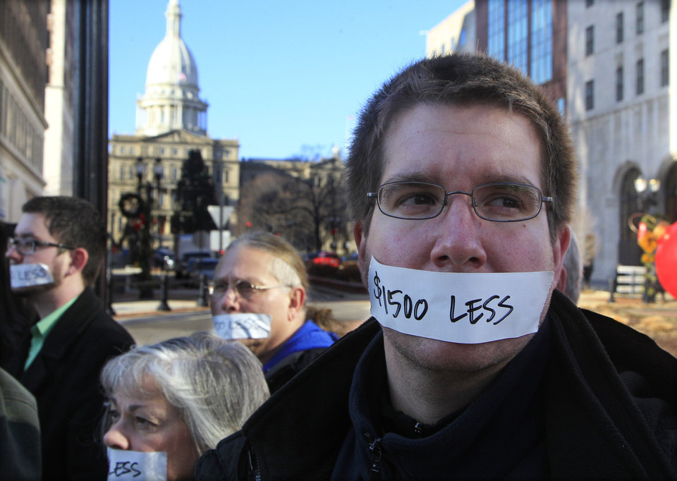 Protesters hold a  silent protest in Lansing, Mich., Wednesday, Dec. 12, 2012, a day after thousands of protesters rallied on the grounds as lawmakers pushed final versions of right-to-work legislation. The tape over their mouths shows how Gov. Rick Snyder and his allies have silenced Michigan�s middle class, and effectively cut the wages of Michiganders by $1500. (AP Photo/Carlos Osorio)