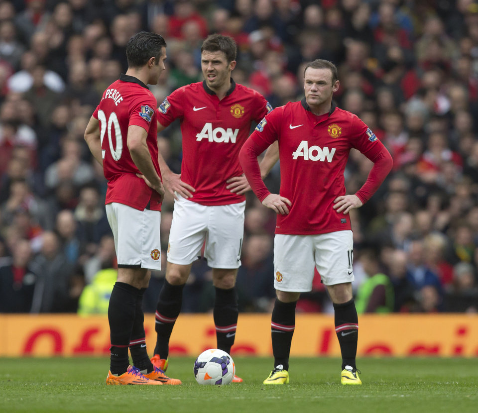 Photo - Manchester United's Wayne Rooney, right, Michael Carrick, centre, and Robin van Persie wait for play to restart after Liverpool's first goal during their English Premier League soccer match at Old Trafford Stadium, Manchester, England, Sunday March 16, 2014. Liverpool won the game 3-0. (AP Photo/Jon Super)