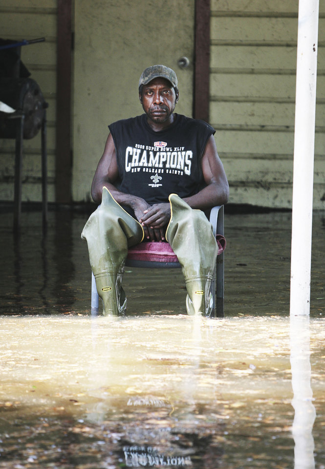 Photo - Michael Washington, a resident of South 10th Street, Monroe, La., sits in his carport on Wednesday, April 27, 2011. Heavy rains Tuesday caused major flooding in the area. Washington says he has not seen flooding this detrimental in the 12 years he has called this residence his home. (AP Photo/The News-Star, Ben Corda)