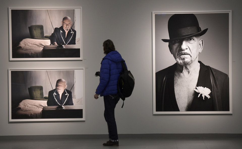 Photo - A visitor looks at pictures of actor Ben Kingsley photographed by Canadian rock star Bryan Adams during the opening of the exhibition