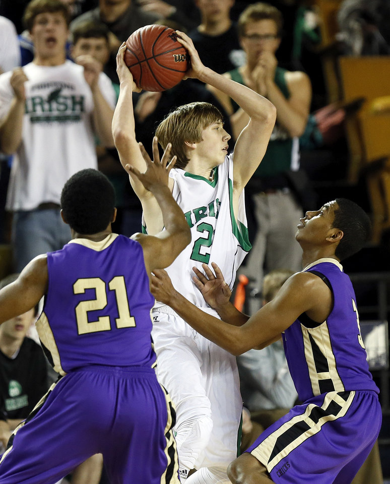 Bishop McGuinness' Brian Canfield (21) looks to pass away from Chickasha's Deshawn Young (21) and E.J. Golightly (3) during a Class 5A boys high school basketball game in the semifinals of the state tournament at the Mabee Center in Tulsa, Okla., Friday, March 8, 2013. Bishop McGuinness beat Chickasha, 50-40. Photo by Nate Billings, The Oklahoman