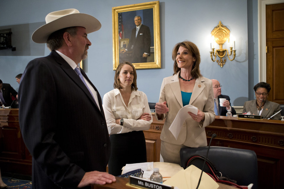 Photo - House Agriculture Committee members, Rep. Doug LaMalfa, R-Calif., left, speaks with Rep. Cheri Bustos, D-Ill., right, on Capitol Hill in Washington, Wednesday, May 15, 2013, prior to the start of the committee's hearing to consider proposals to the 2013 Farm Bill, including small cuts to the $80 billion-a-year food stamp program in an effort to appease conservatives who say the food aid has become too expensive. At center is unidentified aide. (AP Photo/J. Scott Applewhite)