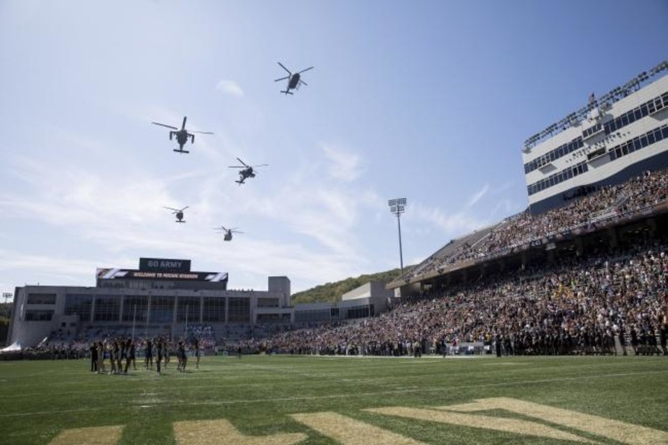 Photo -  Army helicopters flyover Michie Stadium before the start of a game last season against Morgan State. [AP Photo/Julius Constantine Motal]