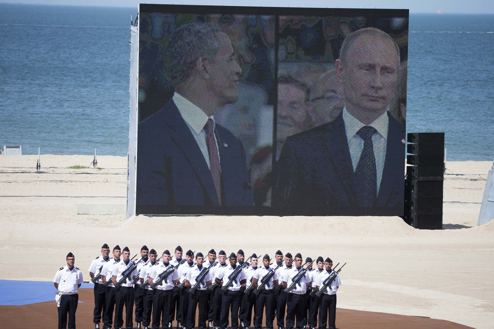 Photo - A giant screen shows US president Barack Obama and Russian President Vladimir Putin on split-screen during an international ceremony marking the 70th anniversary of the Allied landings on D-Day on Sword Beach  in Ouistreham, in Normandy, France, Friday, June 6 June 2014. World leaders and veterans gathered by the beaches of Normandy on Friday to mark the 70th anniversary of World War Two's D-Day landings. (AP Photo/Ian Langsdon, Pool)
