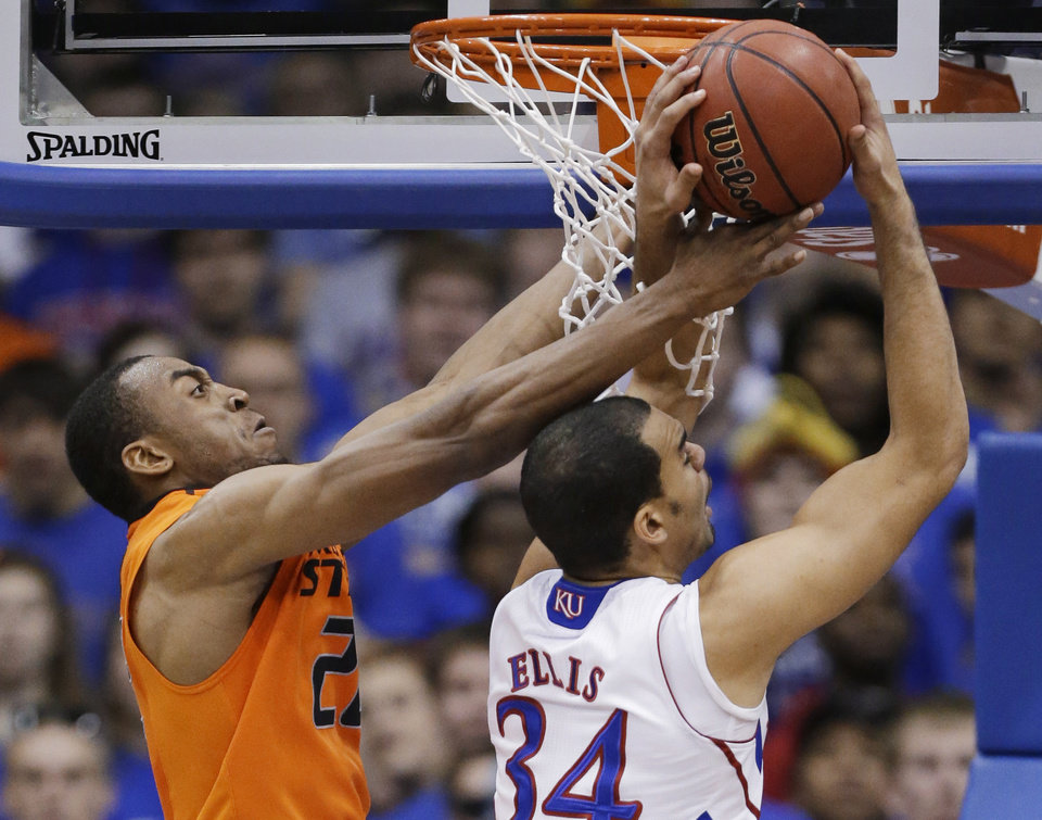 Oklahoma State guard Markel Brown (22) blocks a shot by Kansas forward Perry Ellis (34) during the second half of an NCAA college basketball game in Lawrence, Kan., Saturday, Feb. 2, 2013. Oklahoma State won 85-80. (AP Photo/Orlin Wagner) ORG XMIT: KSOW110