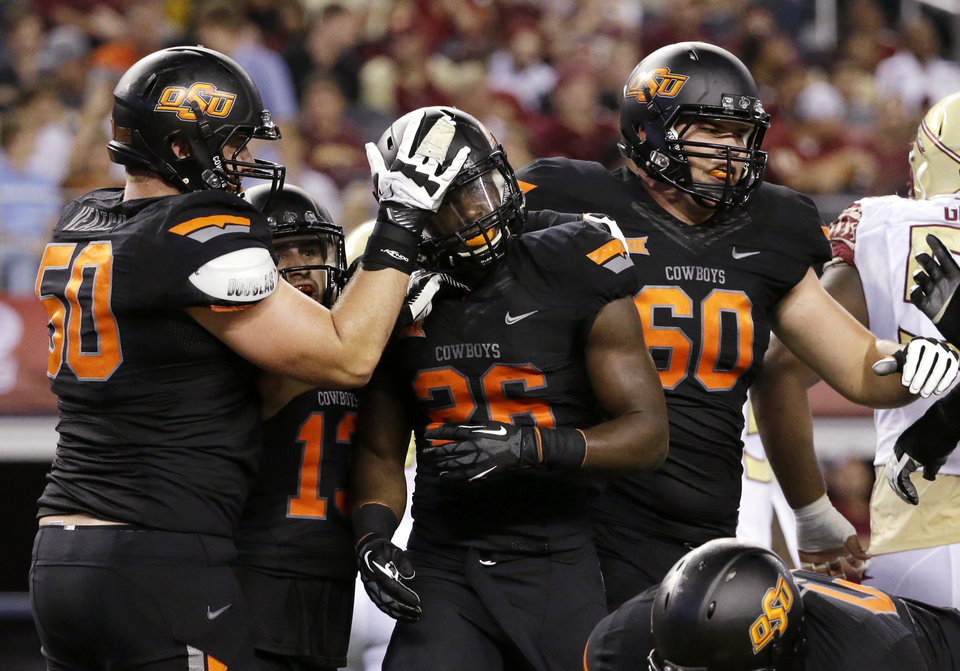 Photo - Oklahoma State's Zac Veatch (50), David Glidden (13) and Cody Jay (60) congratulate P.J. Williams (26) on his short run for a touchdown against Florida State in the first half of an NCAA college football game, Saturday, Aug. 30, 2014, in Arlington, Texas. (AP Photo/Tony Gutierrez)