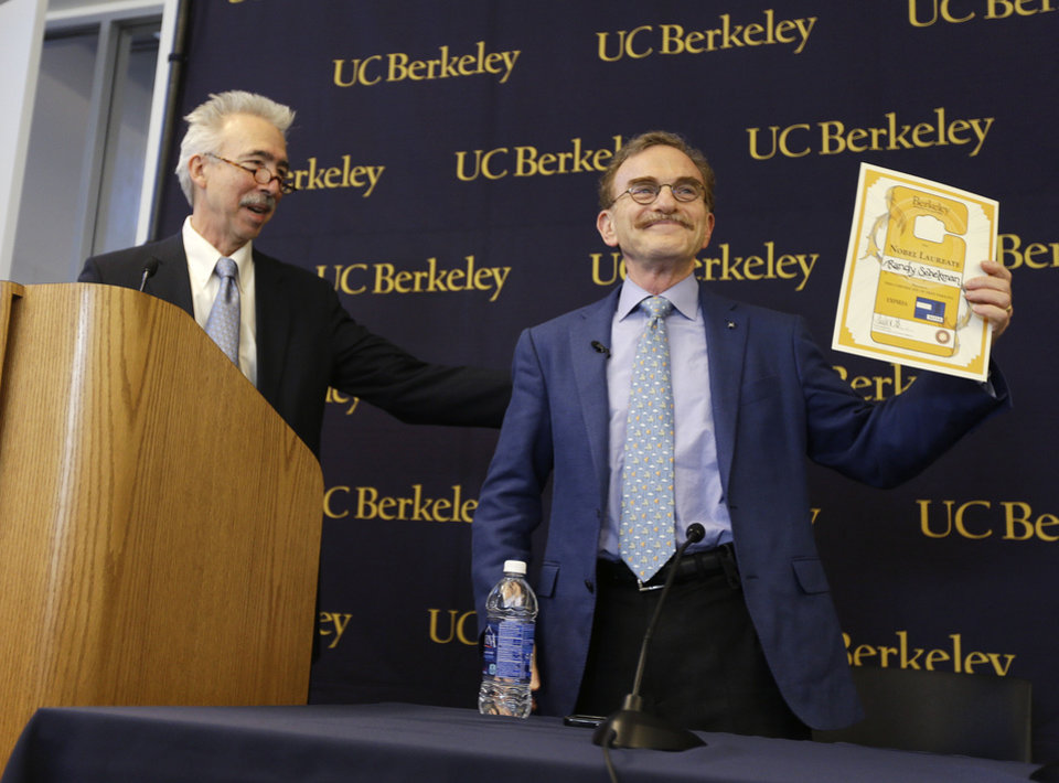 Photo - Randy Schekman, right, professor at the University of California, Berkeley, holds up his lifetime campus parking pass that he was given by Chancellor Nicholas Dirks, left, after winning the Nobel Prize in medicine during a news conference Monday, Oct. 7, 2013, in Berkeley, Calif. Two Americans and a German-American won the Nobel Prize in medicine Monday for discovering how key substances are transported within cells, a process involved in such important activities as brain cell communication and the release of insulin. James Rothman, 62, of Yale University, Randy Schekman, 64, of the University of California, Berkeley, and Dr. Thomas Sudhof, 57, of Stanford University shared the $1.2 million prize. (AP Photo/Eric Risberg)