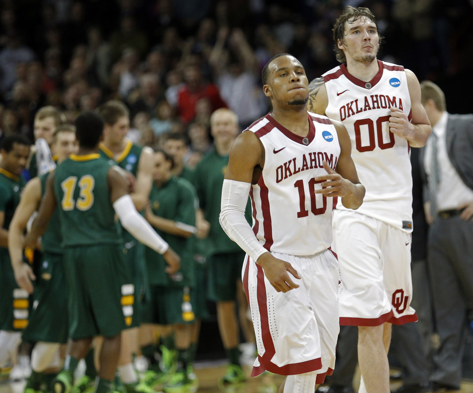 Photo - Oklahoma's Jordan Woodard (10) and Ryan Spangler (00) walk off the court in the final seconds of overtime during the NCAA men's basketball tournament game between the University of Oklahoma and North Dakota State at the Spokane Arena in Spokane, Wash., Thursday, March 20, 2014. Oklahoma home lost 80-75. Photo by Sarah Phipps, The Oklahoman
