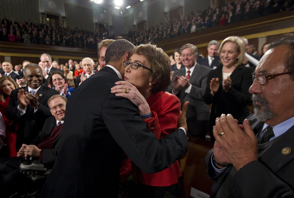 Photo - President Barack Obama embraces retiring Rep. Gabrielle Giffords, D-Ariz., as members of Congress applaud before his State of the Union address in front of a joint session of Congress Tuesday, Jan. 24, 2012, on Capitol Hill in Washington. (AP Photo/Saul Loeb) ORG XMIT: WX157
