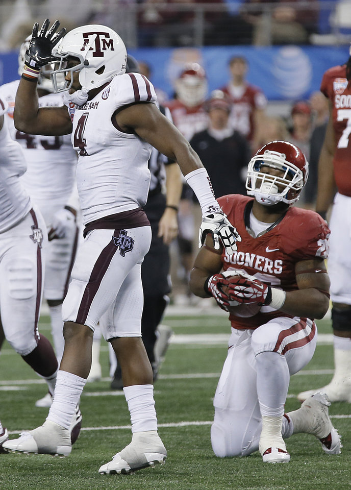 Texas A&M's Toney Hurd Jr. (4) reacts after a stop on Oklahoma's Damien Williams (26) during the college football Cotton Bowl game between the University of Oklahoma Sooners (OU) and Texas A&M University Aggies (TXAM) at Cowboy's Stadium on Friday Jan. 4, 2013, in Arlington, Tx. Photo by Chris Landsberger, The Oklahoman