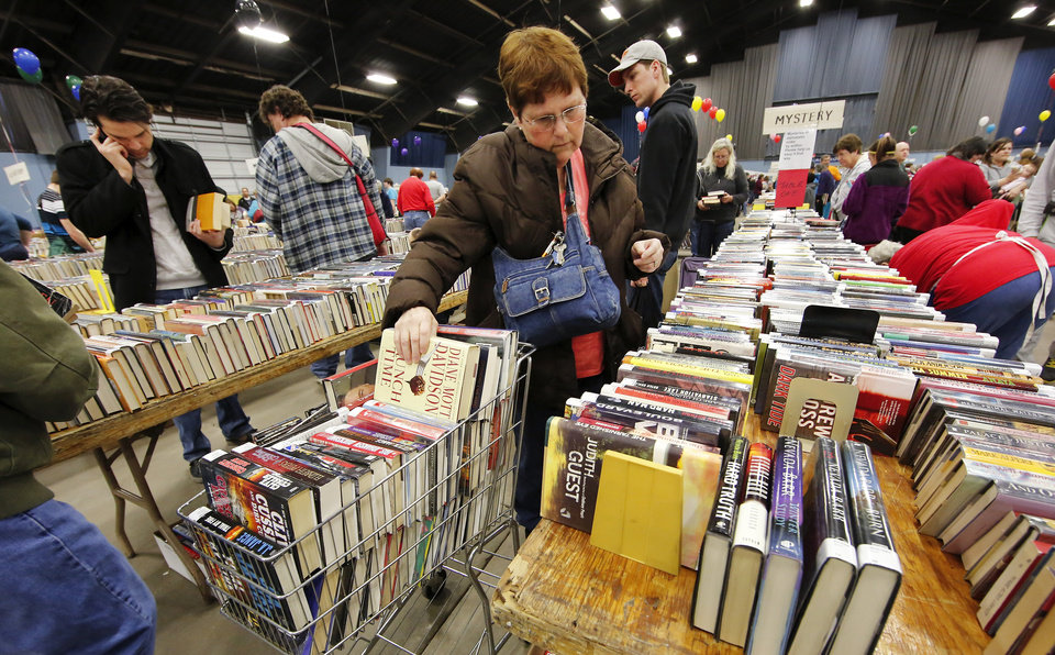 """Linda McCormack places a book in her shopping cart, already full of books.  McCormack drove to the sale from Granite. She said her first sale was five years ago and she knew then she was """"hooked."""" She buys books for her personal use and said she comes to the sale to """"buy a year's worth of reading at one time."""" She said her house looks like a library.  Several thousand bibliophiles and bargain hunters crowded into Oklahoma Expo Hall at State Fair Park on Saturday, Feb. 23, 2013,  in a quest to find reading material  at deeply discounted  prices.  Friends of the Metropolitan Library System is holding their much-anticipated annual book sale this weekend. The sale continues Sunday from 9 a.m. to 5:30 p.m.   Photo by Jim Beckel, The Oklahoman"""