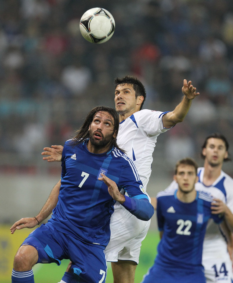Greece's Giorgos Samaras, left, and Bosnia-Herzegovina's Mensur Mujdza challenge for the ball during their World Cup Group G qualifying soccer match at the Karaiskaki stadium in Piraeus port, near Athens, Thursday, Oct. 11, 2012. (AP Photo/Thanassis Stavrakis)