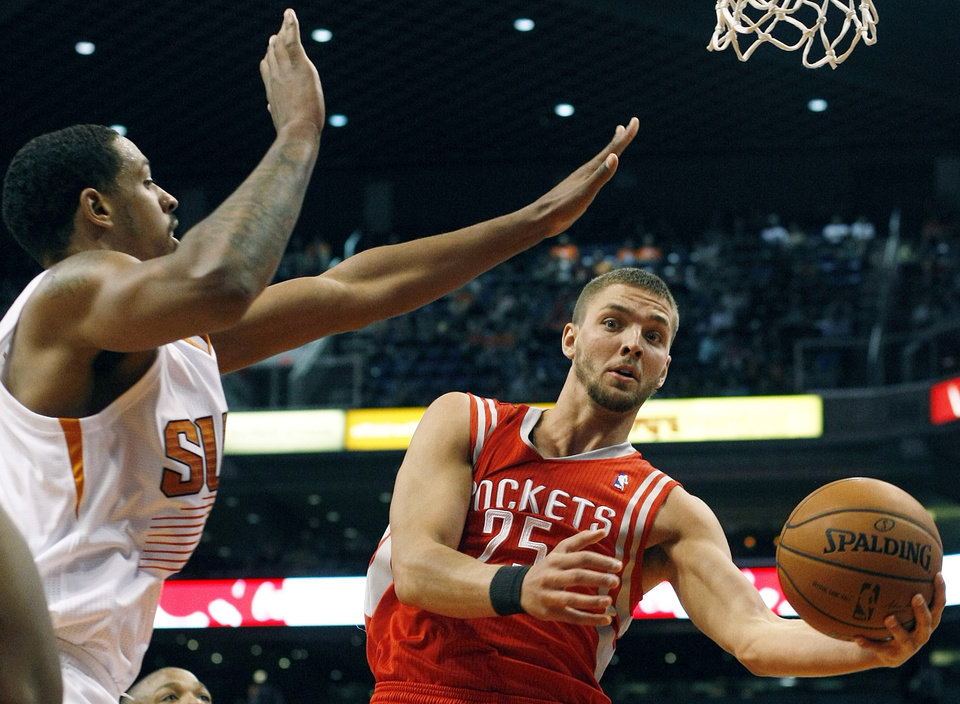 Photo - Houston Rockets forward Chandler Parsons (25) drives on Phoenix Suns forward Channing Frye (8) in the second quarter of an NBA basketball game, Sunday, Feb. 23, 2014, in Phoenix. (AP Photo/Rick Scuteri)