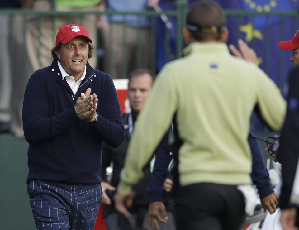 Photo -   USA's Phil Mickelson warms his hands as he greets Europe's Sergio Garcia on the first tee during a foursomes match at the Ryder Cup PGA golf tournament Friday, Sept. 28, 2012, at the Medinah Country Club in Medinah, Ill. (AP Photo/Chris Carlson)
