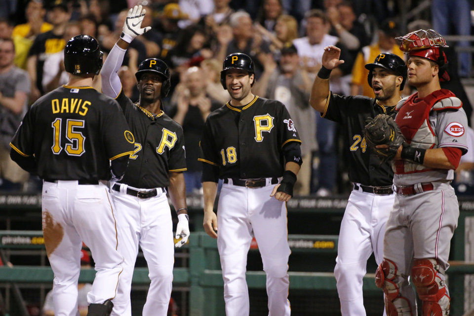 Photo - Pittsburgh Pirates' Ike Davis (15) is celebrates with teammates from left, Andrew McCutchen, Neil Walker (18) and Pedro Alvarez (24), who were on base for his first home run with the Pirates, a grand slam off Cincinnati Reds starting pitcher Mike Leake as Cincinnati Reds catcher Devin Mesoraco watches the scoreboard replay, during the fourth inning of a baseball game in Pittsburgh Monday, April 21, 2014. (AP Photo/Gene J. Puskar)