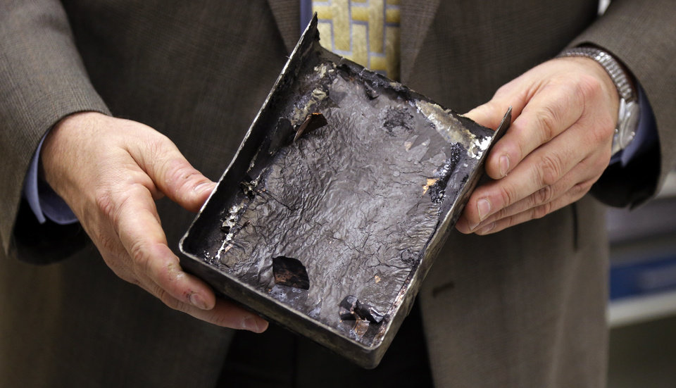 "National Transportation Safety Board's Joseph Kolly, holds an fire-damaged battery casing from the Japan Airlines Boeing 787 Dreamliner that caught fire at Logan International Airport in Boston, at the NTSB laboratory in Washington, Thursday, Jan. 24, 2013. The battery that caught fire in Boston shows evidence of short-circuiting and a chemical reaction known as ""thermal runaway,"" in which an increase in temperature causes progressively hotter temperatures, federal accident investigators said. However, it's not clear to investigators which came first, the short-circuiting or the thermal runaway. (AP Photo/Manuel Balce Ceneta)"