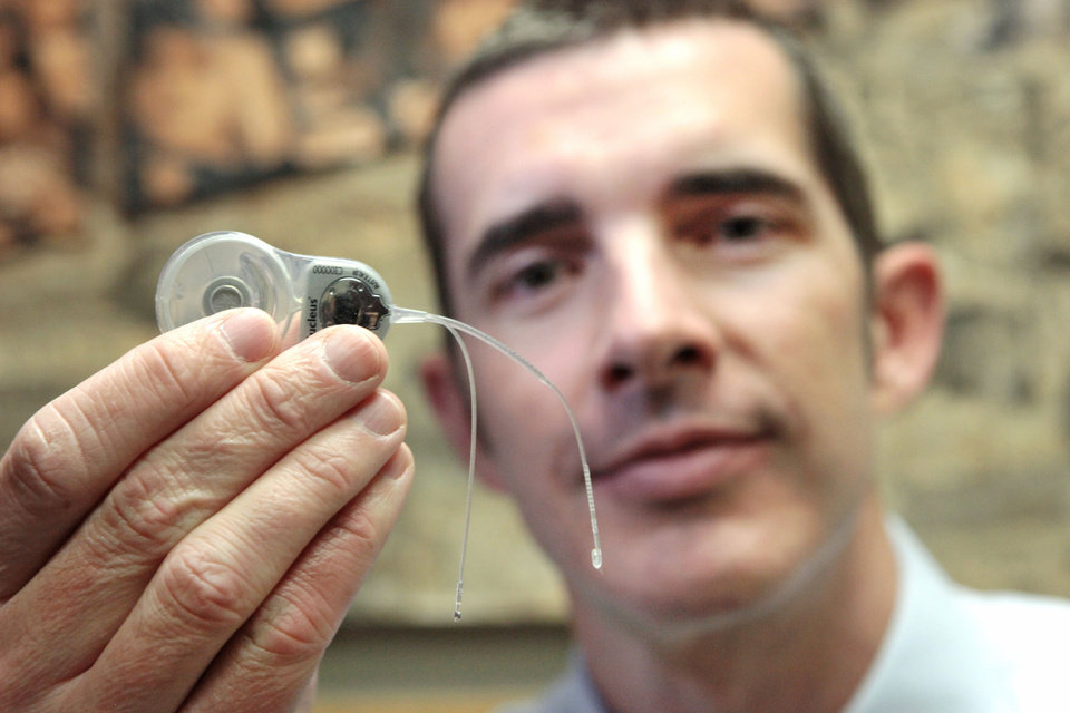 Photo - Jace Wolfe, director of audiology at Hearts for Hearing, holds a cochlear implant. The device can help someone who is severely hard of hearing or deaf begin to hear again, although the sounds might be different from what they remember.  David McDaniel - The Oklahoman