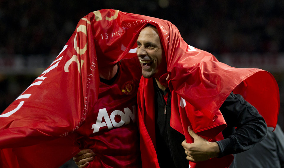 Photo - Manchester United's Rio Ferdinand, right, and Michael Carrick celebrate as they win their 20th English Premier League title after their 3-0 win over Aston Villa in their soccer match at Old Trafford Stadium, Manchester, England, Monday April 22, 2013. (AP Photo/Jon Super)