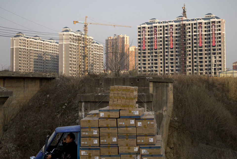 Photo - FILE - In this Monday, Jan. 20, 2014, file photo, a man talks on a mobile phone inside his tricycle cart loaded with goods near under-construction residential buildings in Changsha, in China's Hunan province. U.S. investors are being hit with new worries from overseas just as the economy at home appears to be strengthening. (AP Photo/Andy Wong, File)