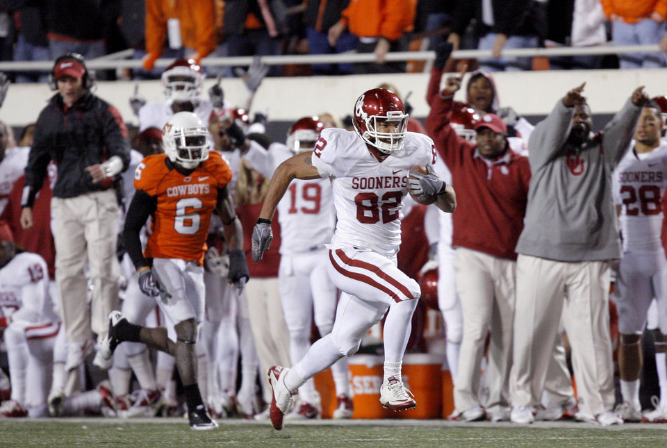 Photo - Oklahoma's James Hanna (82) runs in for a touchdown at Oklahoma State's Andrew McGee (6) chases him during the Bedlam college football game between the University of Oklahoma Sooners (OU) and the Oklahoma State University Cowboys (OSU) at Boone Pickens Stadium in Stillwater, Okla., Saturday, Nov. 27, 2010. Photo by Sarah Phipps, The Oklahoman