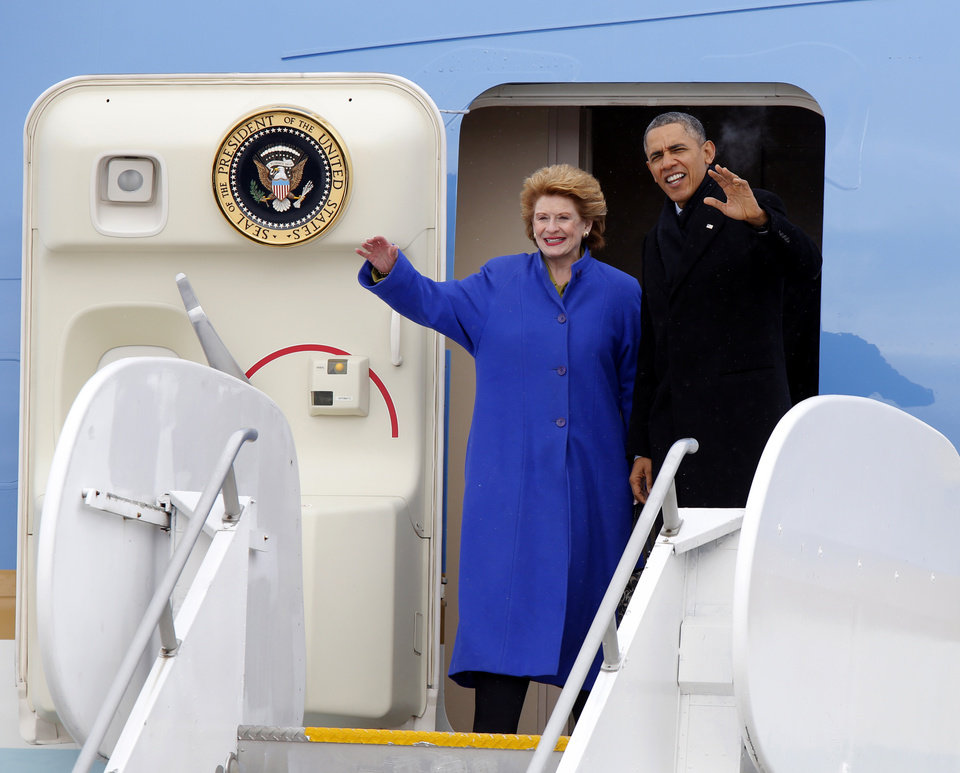 Photo - President Barack Obama, and Senate Agriculture Committee Chair Sen. Debbie Stabenow, D-Mich. wave from Air Force One upon their arrival at Capital City Airport in Lansing, Mich., Friday, Feb. 7, 2014. (AP Photo/Duane Burleson)