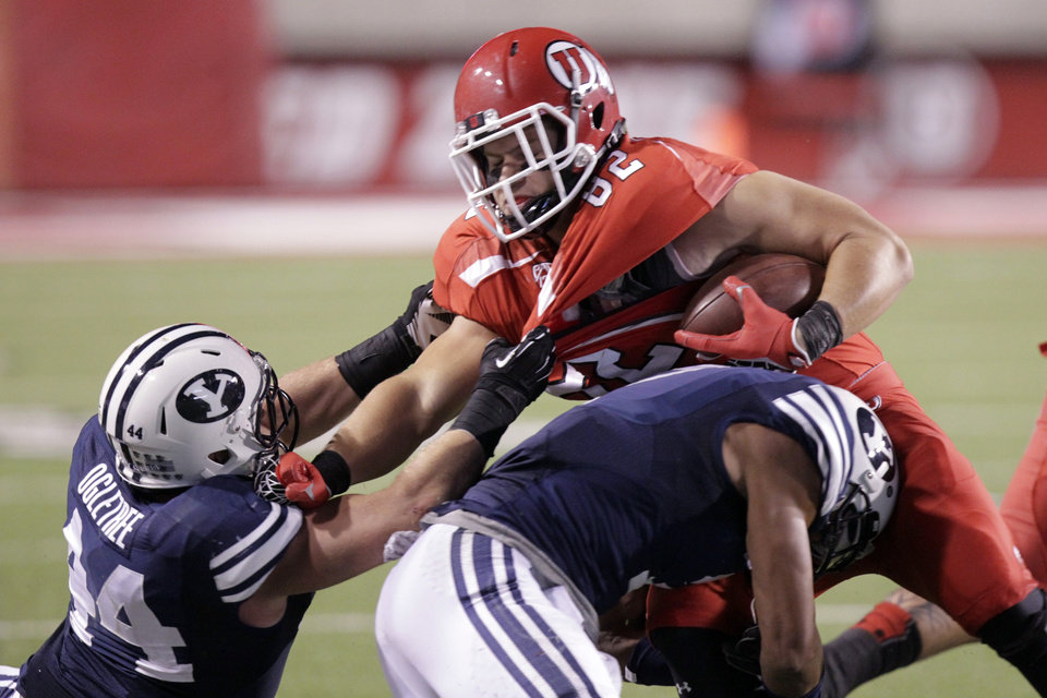 Photo -   Utah tight end Jake Murphy (82) is dragged down by BYU linebacker Brandon Ogletree (44) during the second quarter of an NCAA college football game Saturday, Sept. 15, 2012, in Salt Lake City. (AP Photo/Rick Bowmer)