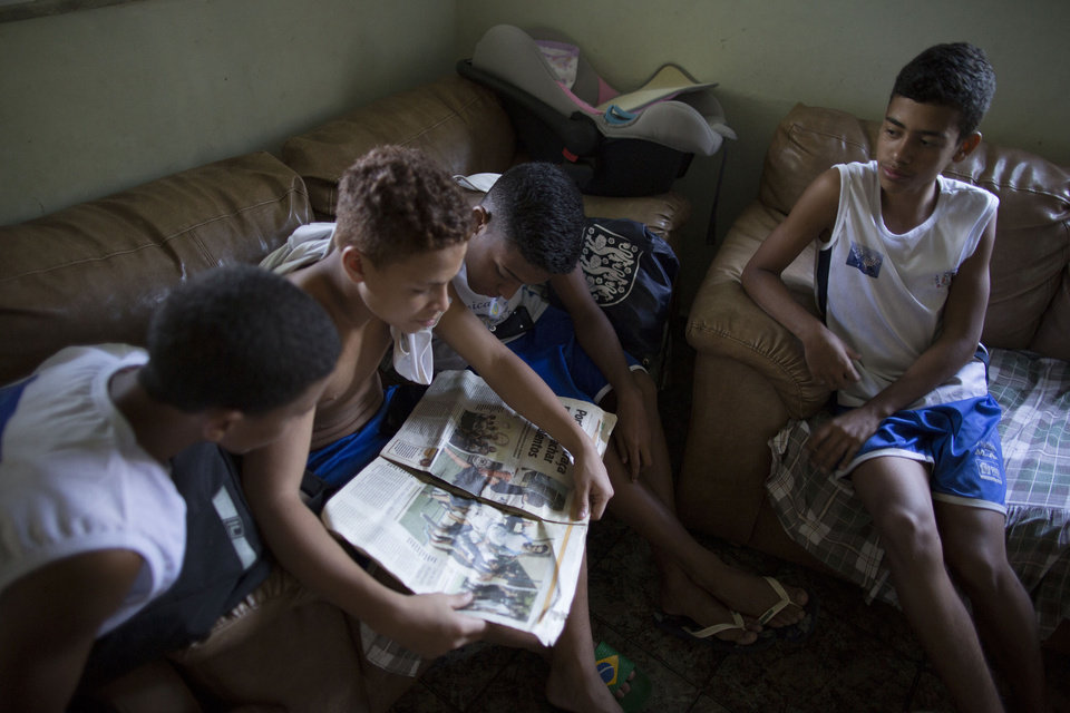Photo - In this June 17, 2014 photo, Andre Rodrigues de Principe, 14, a young soccer player known as Andrezinho to his neighbors, right, sits with his friends reading a local newspaper's article about him, at his home in the Vidigal slum of Rio de Janeiro, Brazil.  Andrezinho got a taste of glory thanks to some stellar dribbling, a skill special enough to have won him a spot in a video released ahead of the World Cup by FIFA. (AP Photo/Leo Correa)